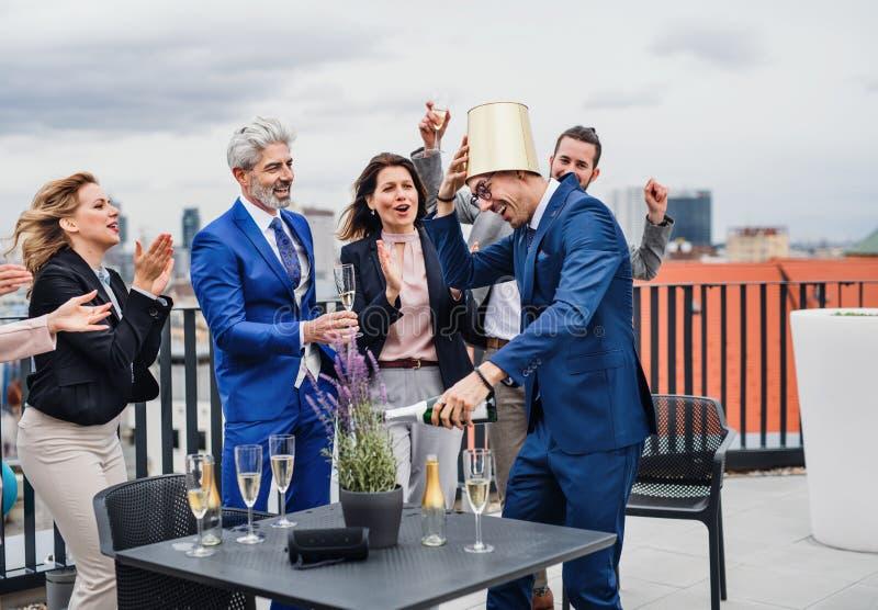 Eine Gruppe frohe Wirtschaftler, die ein Parteifreien auf Dachterrasse in der Stadt haben lizenzfreie stockfotos