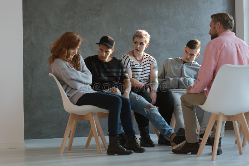 Eine Gruppe Jugendlichen, die ein zurückgezogenes, Selbstachtungsmädchen ermangelnd betrachten lizenzfreie stockfotografie