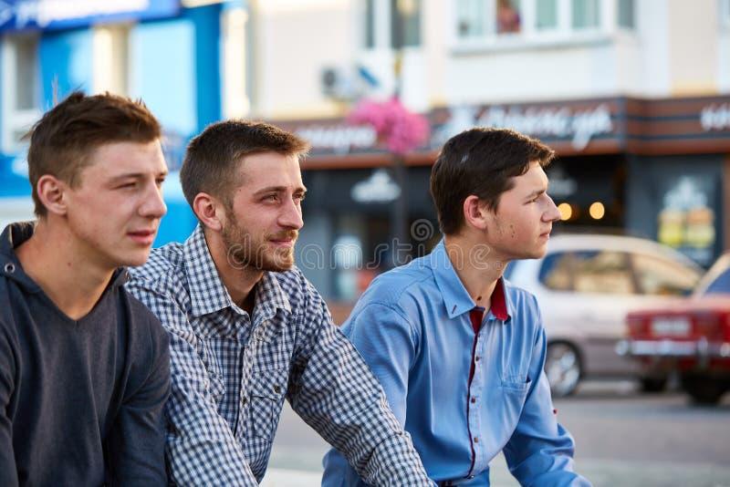 Eine Gruppe Jugendlichen, die heraus draußen in der Stadt auf dem Retro- Hintergrund hängen lizenzfreie stockfotografie