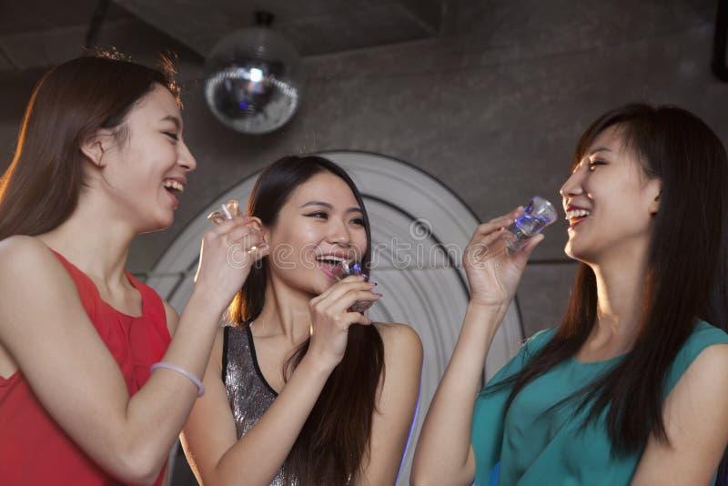 Eine Gruppe junge Frauen, die Schüsse im Nachtklub haben stockfotos
