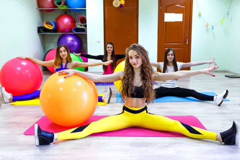 Eine Gruppe junge kaukasische Frauen, die Übungen mit den fitballs legen auf einen Boden in einem Fitness-Club tun stockbild