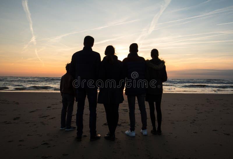 Eine Gruppe junge Leute betrachtet den Sonnenuntergang auf Strand in Katwijk netherlands stockfotos