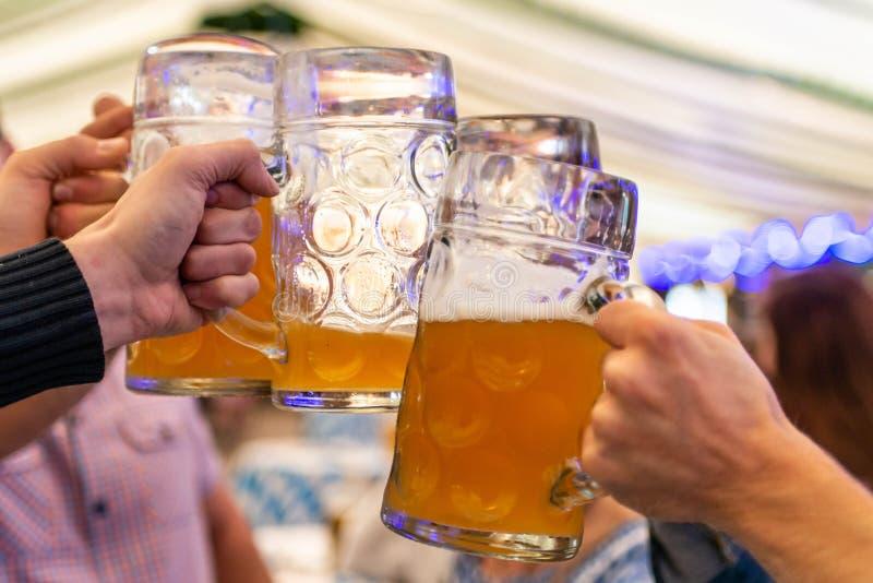 Eine Gruppe junge Leute Freunde, die mit Gläsern Bier an der Weichzeichnung Oktoberfest Deutschland rösten Flacher DOF stockbilder
