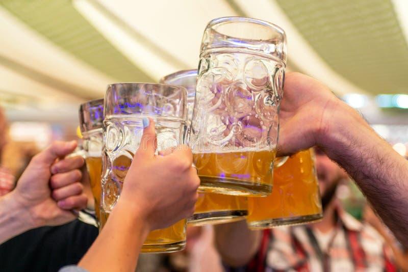 Eine Gruppe junge Leute Freunde, die mit Gläsern Bier an der Weichzeichnung Oktoberfest Deutschland rösten Flacher DOF lizenzfreie stockfotografie