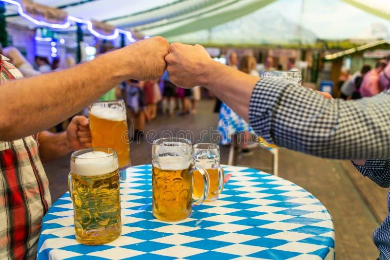 Eine Gruppe junge Leute Freunde, die mit Gläsern Bier an der Weichzeichnung Oktoberfest Deutschland rösten Flacher DOF lizenzfreies stockbild