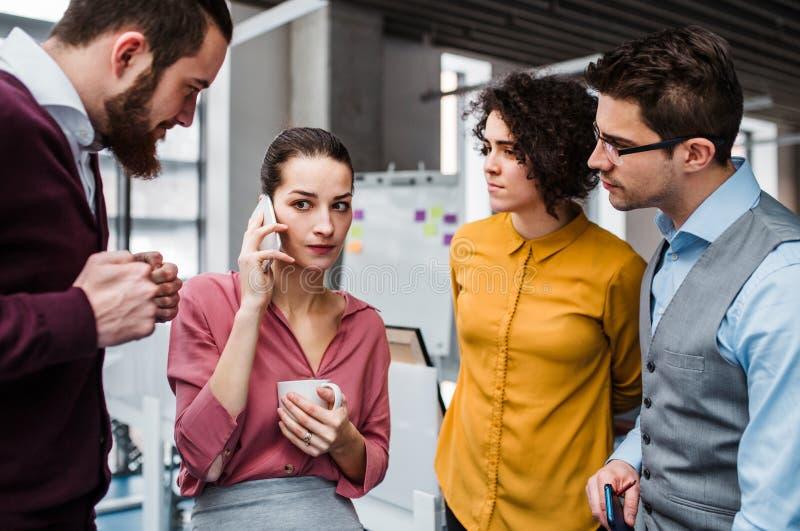 Eine Gruppe junge Wirtschaftler mit Smartphonestellung im Büro, einen Telefonanruf machend lizenzfreies stockbild