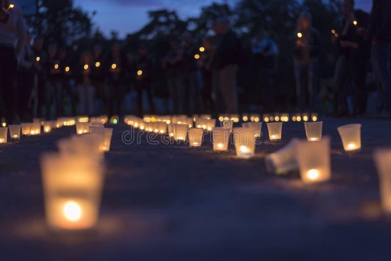 Eine Gruppe Kerzen, die in der Straße und in Leuten halten Kerzen im Hintergrund brennen Tag des Gedächtnisses von beraubt lizenzfreies stockfoto