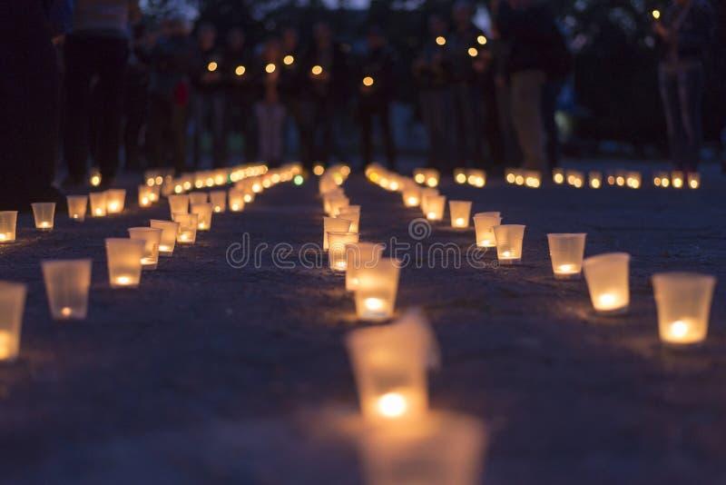 Eine Gruppe Kerzen, die in der Straße und in Leuten halten Kerzen im Hintergrund brennen Tag des Gedächtnisses von beraubt stockbild