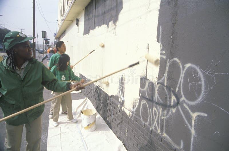 Eine Gruppe Kinder, welche die Seite eines Gebäudes entstellt durch Graffiti neu streichen lizenzfreie stockfotos