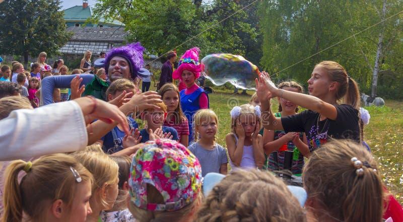 Eine Gruppe Mädchen passen auf, während ein Mädchentrickzeichner eine große Seifenblase an einem warmen Herbsttag aufbläst lizenzfreie stockfotos