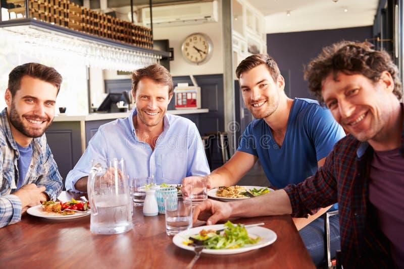 Eine Gruppe Männer, die in einem Restaurant zu Mittag essen stockfotos