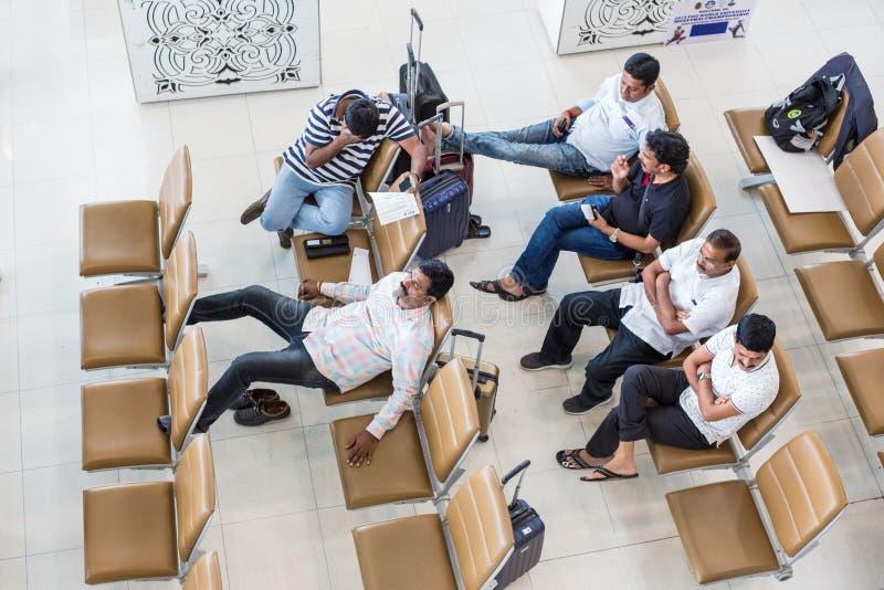 Eine Gruppe männliche indische Touristen warten geduldig ihren Flug lizenzfreie stockfotografie