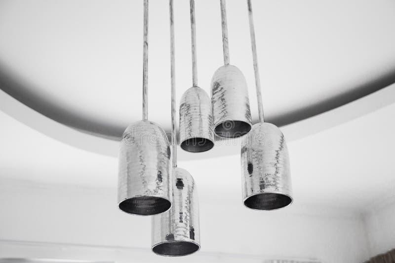 Eine Gruppe mettalic hängende Lichter auf weißer Decke in Dachboden entworfener Wohnung lizenzfreie stockfotografie