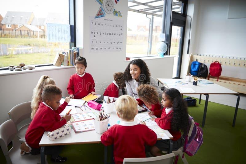 Eine Gruppe Säuglingsschulkinder, die an einem Tisch in einem Klassenzimmer mit ihrem weiblichen Lehrer sitzen lizenzfreie stockfotografie