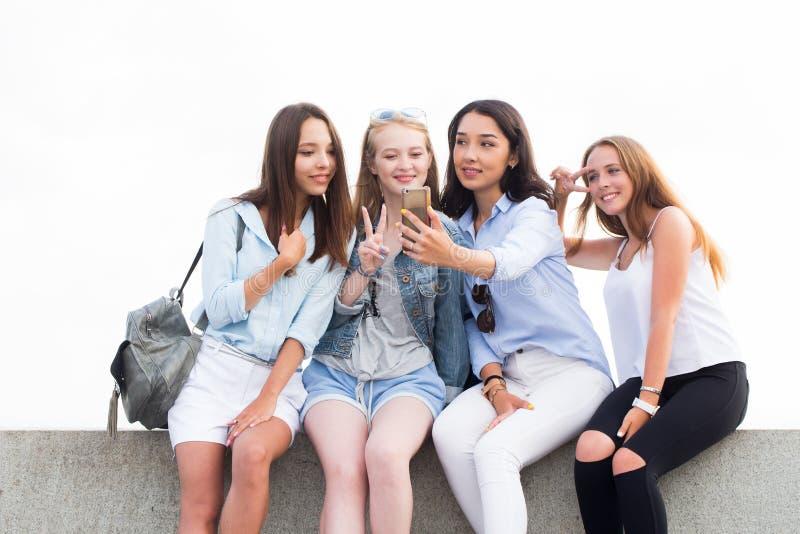 Eine Gruppe Studenten im Park Eine schöne Brunettefrau zeigt ihren Freunden auf ihrem Smartphone etwas Freundschaft und moder stockbilder