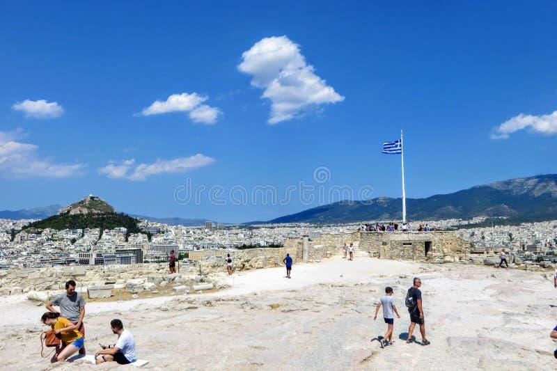 Eine Gruppe Touristen, die um die Akropolis ein heißer sonniger Sommertag mit einer schönen Ansicht der ausbreitenden Stadt von A lizenzfreies stockbild