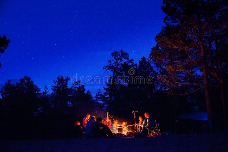 Eine Gruppe Touristen, die um das Lagerfeuer nachts sitzen lizenzfreies stockbild