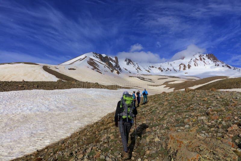 Eine Gruppe Touristen klettert die felsige Steigung des Berges zur Schnee-mit einer Kappe bedeckten Spitze lizenzfreies stockbild