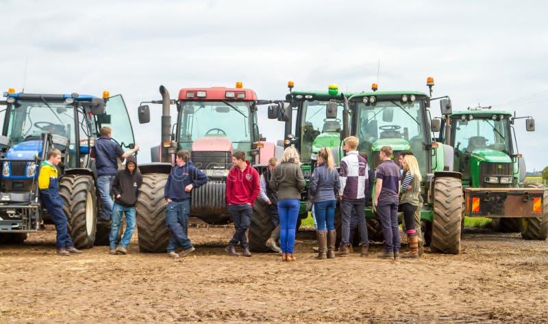 Eine Gruppe Traktoren parkte oben mit jungen Landwirten lizenzfreies stockbild