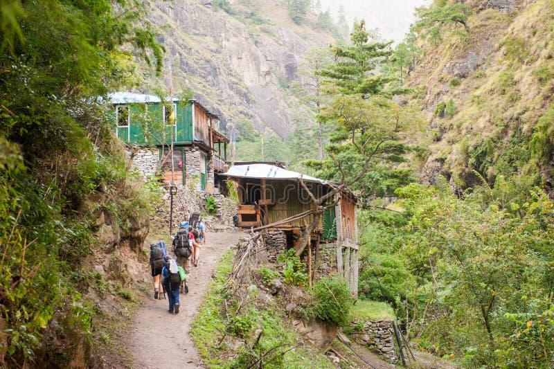 Eine Gruppe Trekkers, die zu Lho-Dorf auf Manaslu-Stromkreis mit Ansicht des Bergs Manaslu vorangehen, erstrecken sich 8 156 Mete lizenzfreies stockbild