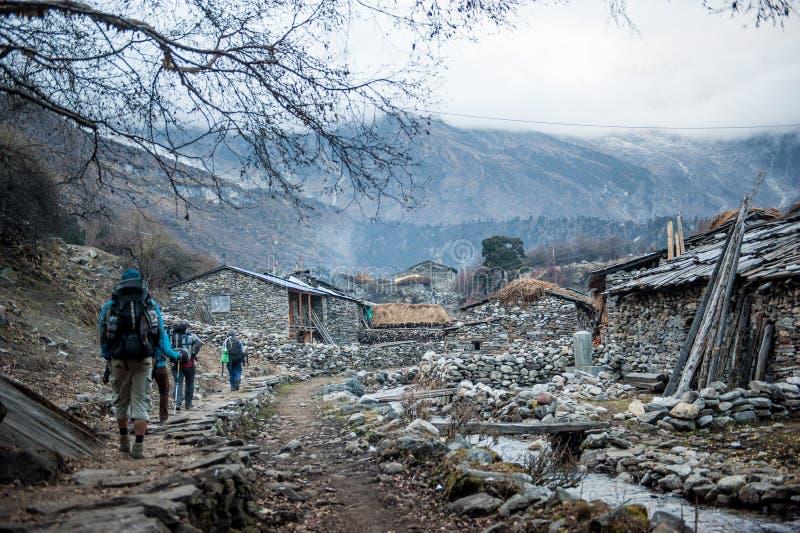 Eine Gruppe Trekkers, die zu Samagau-Dorf auf Manaslu-Stromkreis mit Ansicht des Bergs Manaslu vorangehen, erstrecken sich 8 156  lizenzfreies stockfoto