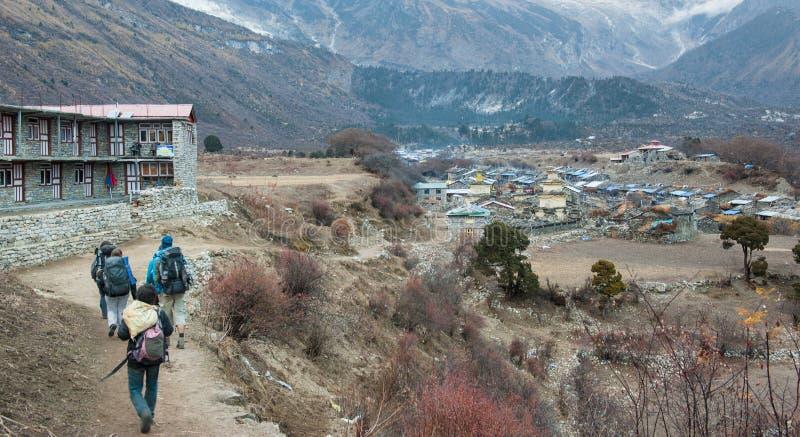 Eine Gruppe Trekkers, die zu Samagau-Dorf auf Manaslu-Stromkreis mit Ansicht des Bergs Manaslu vorangehen, erstrecken sich 8 156  lizenzfreie stockfotografie