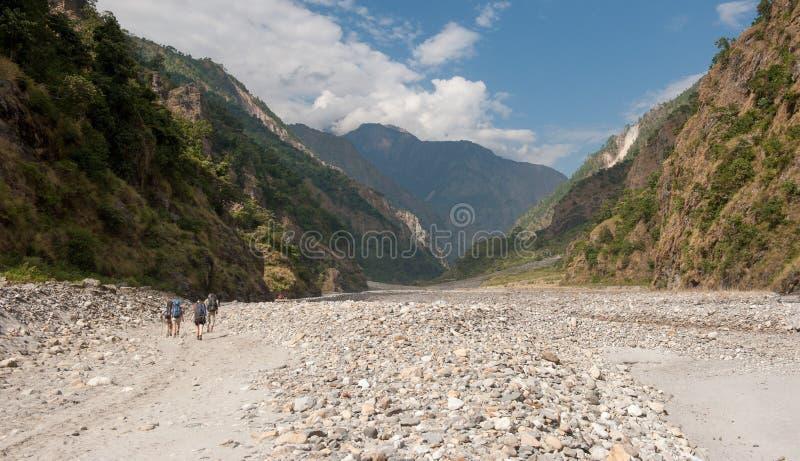 Eine Gruppe Trekkers im Flussbett auf Manaslu-Stromkreis mit Ansicht des Bergs Manaslu erstrecken sich 8 156 Meter Himalaja, Mana stockbild