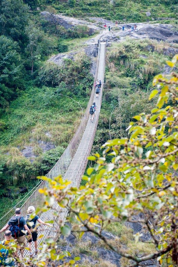Eine Gruppe Trekkers, welche die Brücke im Tal mit Fluss auf Manaslu-Stromkreis mit Ansicht des Bergs Manaslu kreuzen, erstrecken lizenzfreies stockbild