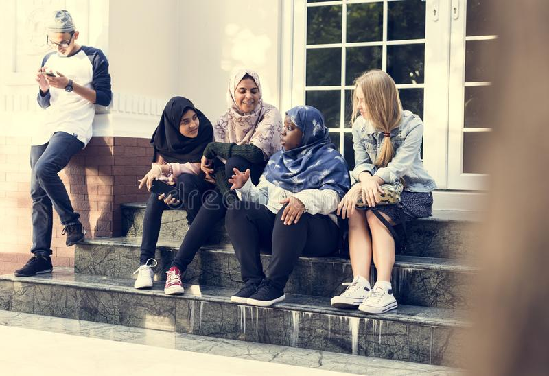 Eine Gruppe verschiedene Jugendlichen, die vor dem Gebäude sprechen lizenzfreie stockbilder