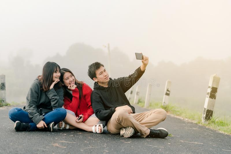 Eine Gruppe von drei asiatischen Freunden, die eine Strickjacke unter Verwendung eines selfie Telefons tragen, um Fotos in einer  stockfotografie