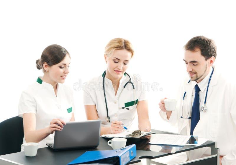 Eine Gruppe von drei jungen Doktoren, die zusammenarbeiten lizenzfreie stockbilder