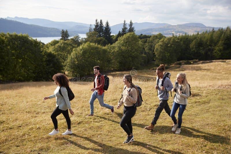Eine Gruppe von fünf jungen erwachsenen Freunden lächeln beim Gehen auf einen ländlichen Weg während einer Bergwanderung, Seitena lizenzfreie stockbilder