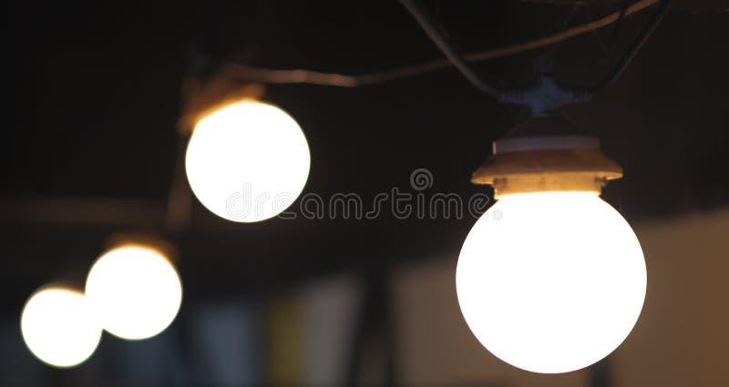 Eine Gruppe von 4 Glühlampen in einer Linie auf einem dunklen Hintergrund lizenzfreies stockbild