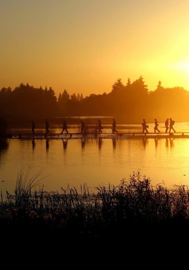 Eine Gruppe von Personen, die auf den Fußweg auf Wasser geht stockfotografie