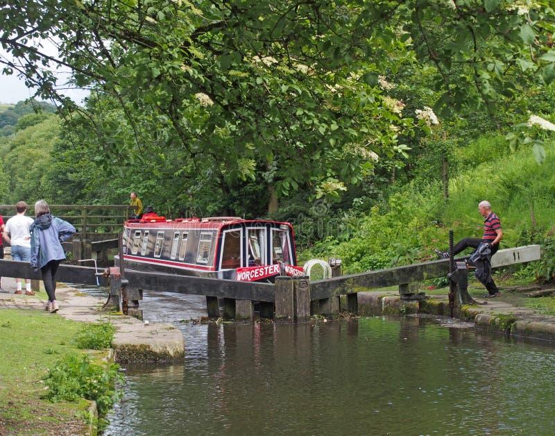 eine Gruppe von Personen, die mit einem Schmalboot durch ein Schleusentor auf dem rochdale Kanal in der Hebden-Brücke West-Yorksh stockbilder