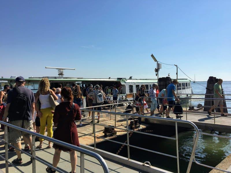 Eine Gruppe von Personen, die wartet, um eine Wasser Fähre oder ein vaporetto auf Murano-Insel, gerade über Venedig, Italien zu v stockbild