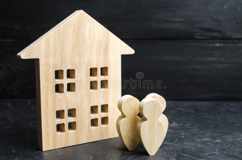Eine Gruppe von Personenen-Stellung nahe dem Wohngebäude Kaufen oder Verkaufs- Unterkunft und Immobilien Leihen, zum eines Hauses stockfotos