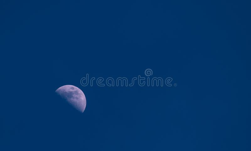 Eine Hälfte des Mondabschlusses oben in der Dunkelheit, Abend, blauer Himmel, Krater und Struktur des Mondes sind sichtbar stockfotografie