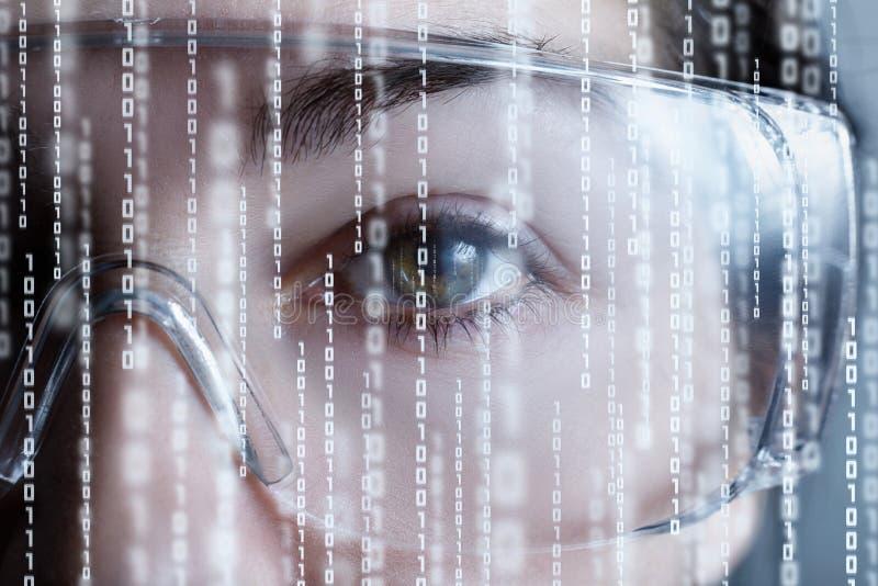Eine Hälfte des weiblichen Gesichtes in den Gläsern der virtuellen Realität mit binär Code stockbild