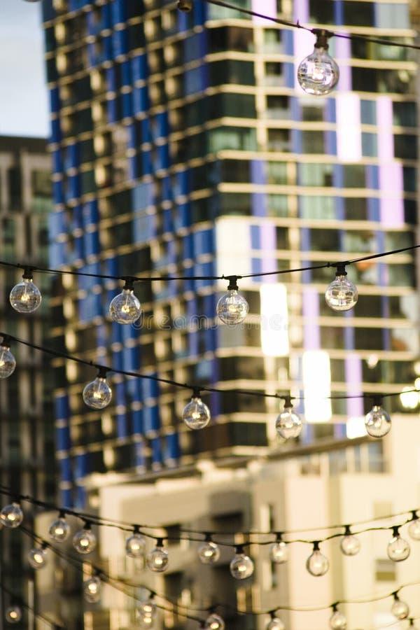 Eine hängende Lichterkette an der Königin Victoria Markets mit den Skylinen von Melbourne-Stadt im Hintergrund lizenzfreies stockbild