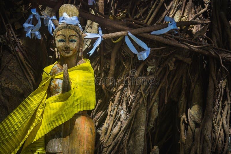 Eine hölzerne Statue eines Beten oder Meditation Geistes der Bäume, Mädchen Baum mit weißen Bändern Thailändisches Gruß wai Hande lizenzfreie stockfotos
