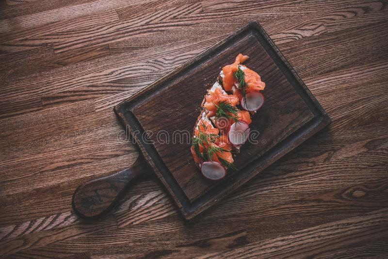 Eine hölzerne Tischplatte, auf der ein Brett von Sandwichen mit Salmo liegt stockbild