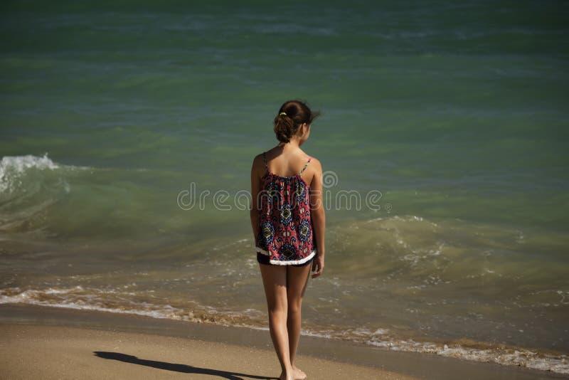 Eine h?bsche M?dchenstellung auf dem Strand und Untersuchung weit das Meer, weiches fockus stockbild