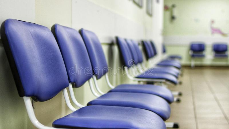 Eine Halle in einem Krankenhaus, Stühle für die Patienten, die warten, um einen Doktor, Reihen zu sehen von blauen Stühlen stockbilder