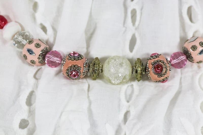 Eine Halskette des aufwändigen Pfirsiches färbte die Perlen, die auf eine weiße Ösenbluse - Nahaufnahme und selektiver Fokus lege lizenzfreies stockbild
