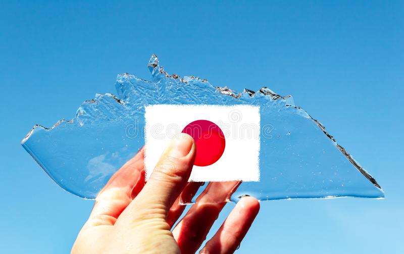 Eine Hand, die dünnes transparentes Stück Eis in Form eines Eisbergs mit der Flagge des Japans gegen einen blauen Himmel hält Das stockfotos