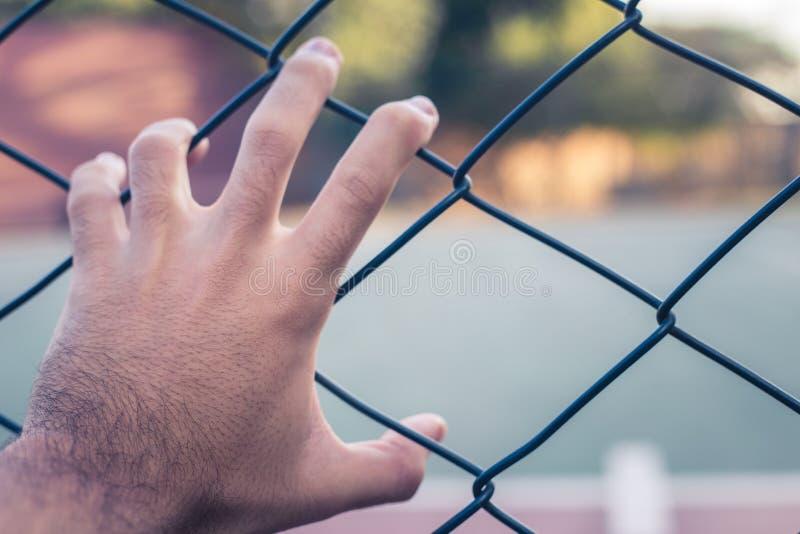 Eine Hand, die ein Metallgitter hält stockfotografie