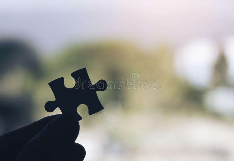 Eine Hand, die ein Puzzlen mit Unschärfehintergrund hält lizenzfreie stockbilder