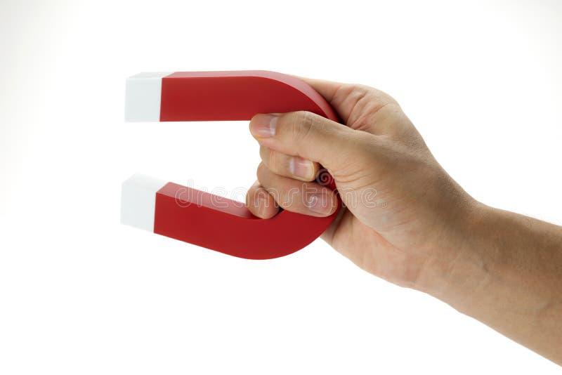 Eine Hand, die einen Magneten lokalisiert auf Weiß, um einen Gegenstand aufzuheben hält stockfoto