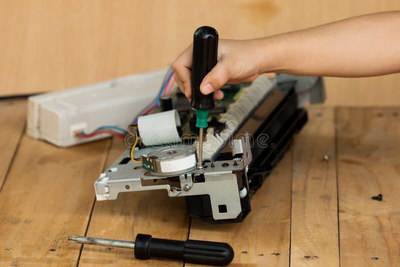 Eine Hand, die einen Schraubenzieher hält, installiert oder repariert stockbilder